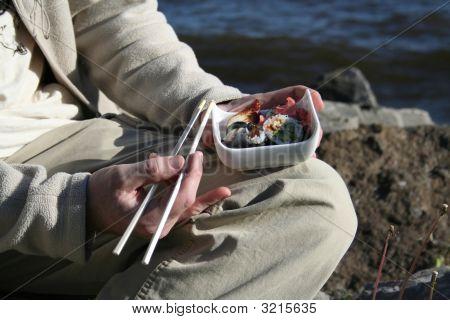 Man Eating Sushi Sitting On A Beach