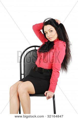 Schönes Mädchen tragen Rock und roten Hemd sitzt auf Stuhl und berührt ihr Haar im Studio