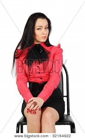 Beautiful Evil Girl Wearing Skirt And Red Shirt Sits On Chair In Studio