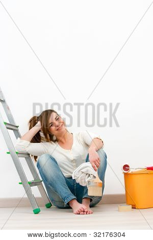 Young Woman Painter Sitting On Floor After Painting.