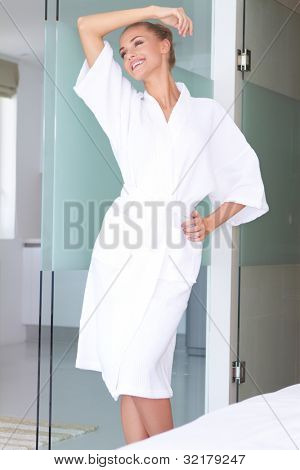 Smiling woman standing in white bathrobe in modern room