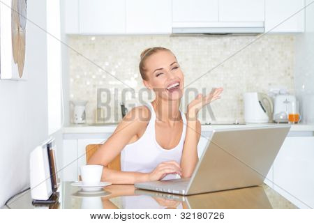 Laughing woman sitting at her laptop computer in her kitchen enjoying something she has just read over the internet