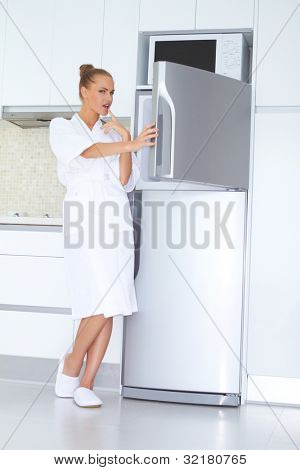 Vivacious woman in a white bathrobe and slippers standing laughing as she opens the freezer unit of her refrigerator
