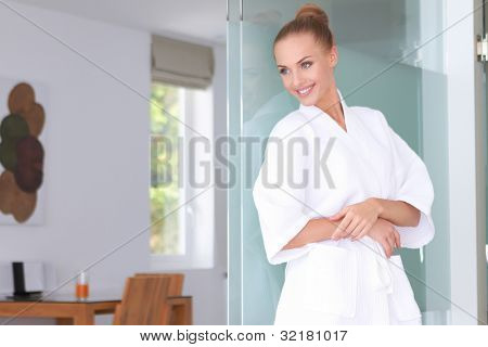 Beautiful woman standing in white bathrobe in modern room