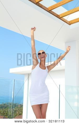 Shapely woman in skimpy mini skirt and dark glasses standing on an outdoor summer patio raising her arms in jubilation