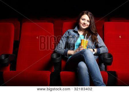 Постер, плакат: Молодая девушка сидит в кино и смотреть фильм, холст на подрамнике