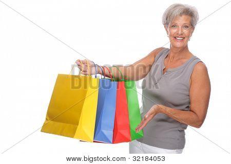 Completo retrato isolado de uma mulher sênior com sacos de compras
