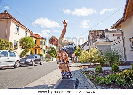 Boy Riding A Skateboard Going Airborne At A Sidewalk
