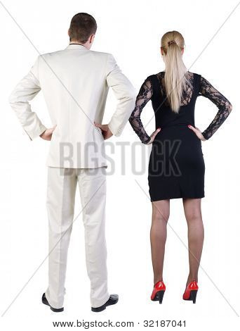 Back view of  business team look into the distance. young couple (man and woman) rear view.  beautiful friendly girl in dress and guy in suit together. Rear view. Isolated over white background.