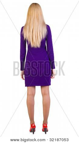 back view of standing beautiful blonde business woman. Young girl in violet dress and red kitten heels. Rear view. Isolated over white background.