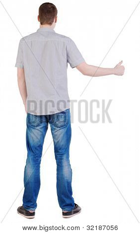 back view of standing Young brunette man showing thumb up. Young guy in jeans and shirt  gesturing ok sign . Rear view. Isolated over white background