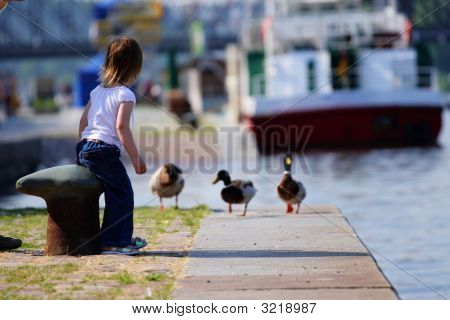 Girl Feeding Ducks At Landing Stage.