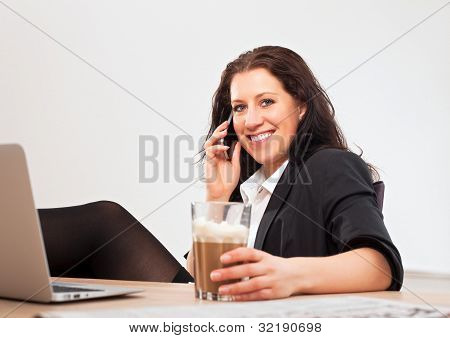 Young Professional Using Her Phone In The Office