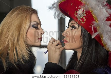 Backstage scene: Professional Make-up artist doing glamour model makeup in colorful stylized medieval costume
