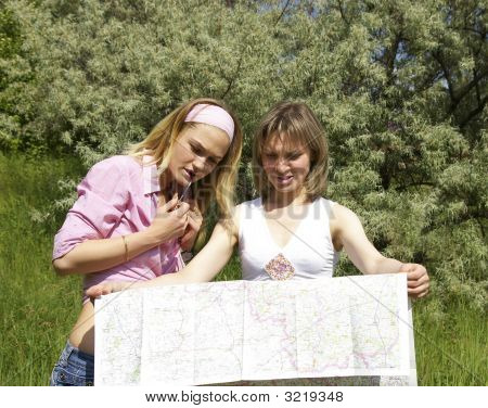 Two Beautiful Girls Look At The Map