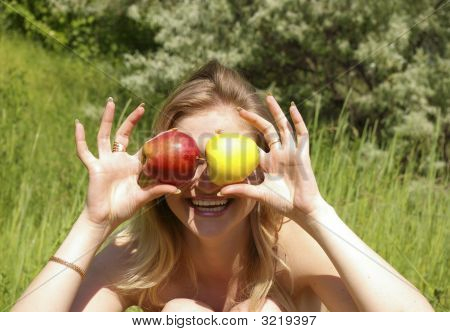 Woman Holding Up Two Apples