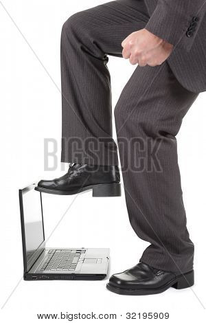 Furious businessman about to stamp on his laptop computer in frustration