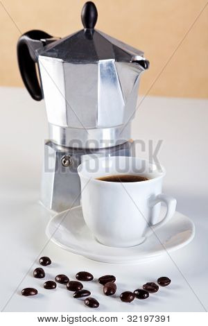 Photo of an Italian Caffettiera or Moka pot with a cup of freshly brewed espresso coffee, a few arabica beans in front. These are also referred to as a Stove pot and are made from aluminium.