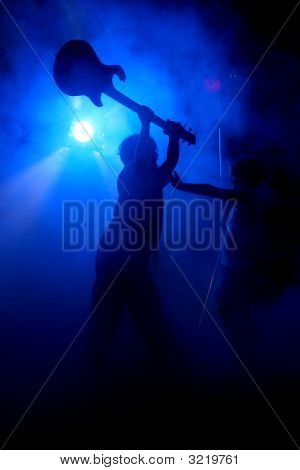 Silhouette Of Siblings Smashing Guitar