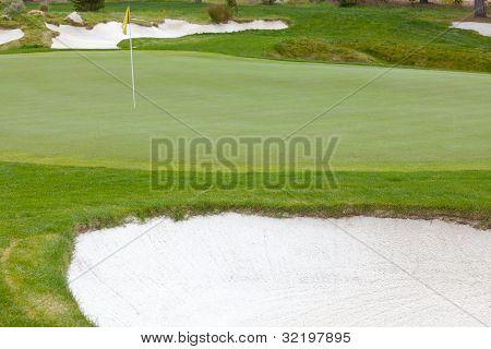 Beautiful Golf Green And Flag Pin Surrounded By Sand Traps