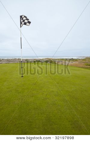 Flag And Putting Green On Coastal Golf Course