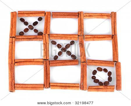 Composition of coffee beans and cinnamon isolated on white. Noughts and crosses.