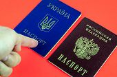 Two National Internal Passports Lying On Red Background, Red Russian Passport And Blue Ukrainian Pas poster