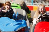image of amusement park rides  - Teenage girls driving a bumper cars - JPG