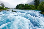 foto of ravines  - Milky blue glacial water of Briksdal River in Norway - JPG