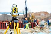 stock photo of theodolite  - Surveying measuring equipment theodolite transit on tripod at construction building area site - JPG