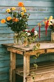 Fall Flowers In Glass Jars Standing On The Table Outside poster