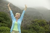 picture of middle-age  - Excited Woman Raising Arms - JPG