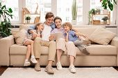 Young joyful casual family of two kids and couple sitting on sofa and watching funny video or cartoo poster
