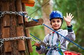 Young Boy Climbing Pass Obstacles In Rope. Child In Forest Adventure Park. poster
