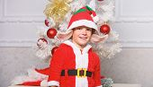 Boy Kid Dressed As Cute Elf Magical Creature White Artificial Ears And Red Hat Near Christmas Tree.  poster