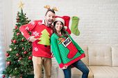 Playful Partners Showing Their Ugly Sweaters While Enjoying Christmas Holiday At Home poster