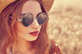 Portrait of a modern hippie girl in a wheat field. Bohemian style. poster