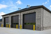 An New Brick Commercial Building With Three Large Garage Doors poster