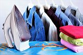 Colored Shirts On A Hanger, Electric Iron, Towels, Ironing Board In The Laundry Room. Ironing Clothe poster