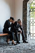 Upset Woman And Sad Man Sitting On Bench On Funeral poster