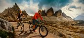 Couple cycling on electric bike, rides mountain trail. Woman and Man riding on bikes in Dolomites mo poster