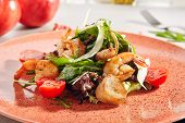 Mixed seafood salad with fried shrimps, arugula, lettuce and cherry tomatoes close up with selective poster