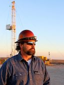 image of derrick  - Oil and natural gas field worker watching the sunset - JPG