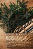 Rustic Basket With Fir Branches And Festive Wrapping Paper On Rustic Wooden Background. Flat Lay. Wi poster
