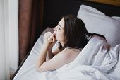 Beautiful Young Woman Having Good Morning In Bed With Clean White Linens In A Cozy Wooden House. She poster