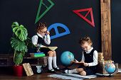 Little Twins In School Uniform And Glasses Reading Interesting Books While Studying Together poster