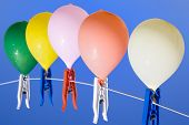 picture of spanking  - Group of colored water filled balloons with waterdrops hanging on a clothesline with a blue sky as background seen from above - JPG