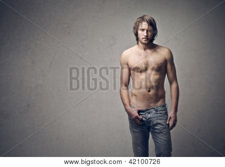 handsome guy shirtless on a gray background