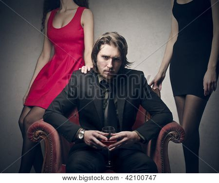 handsome man sitting on chair with two gorgeous women behind