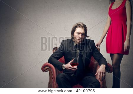 young handsome man sitting on the chair with a glass of red wine and beautiful woman behind